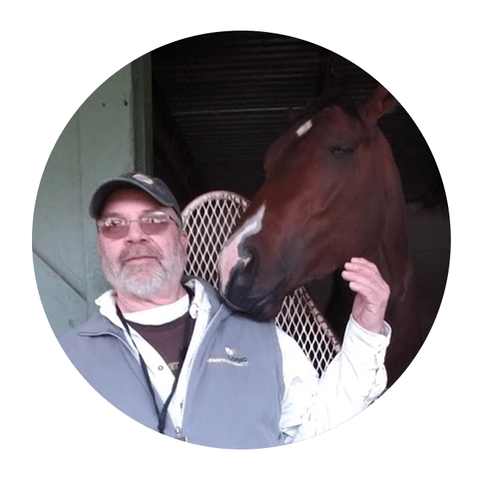 man with beard in front of bay horse