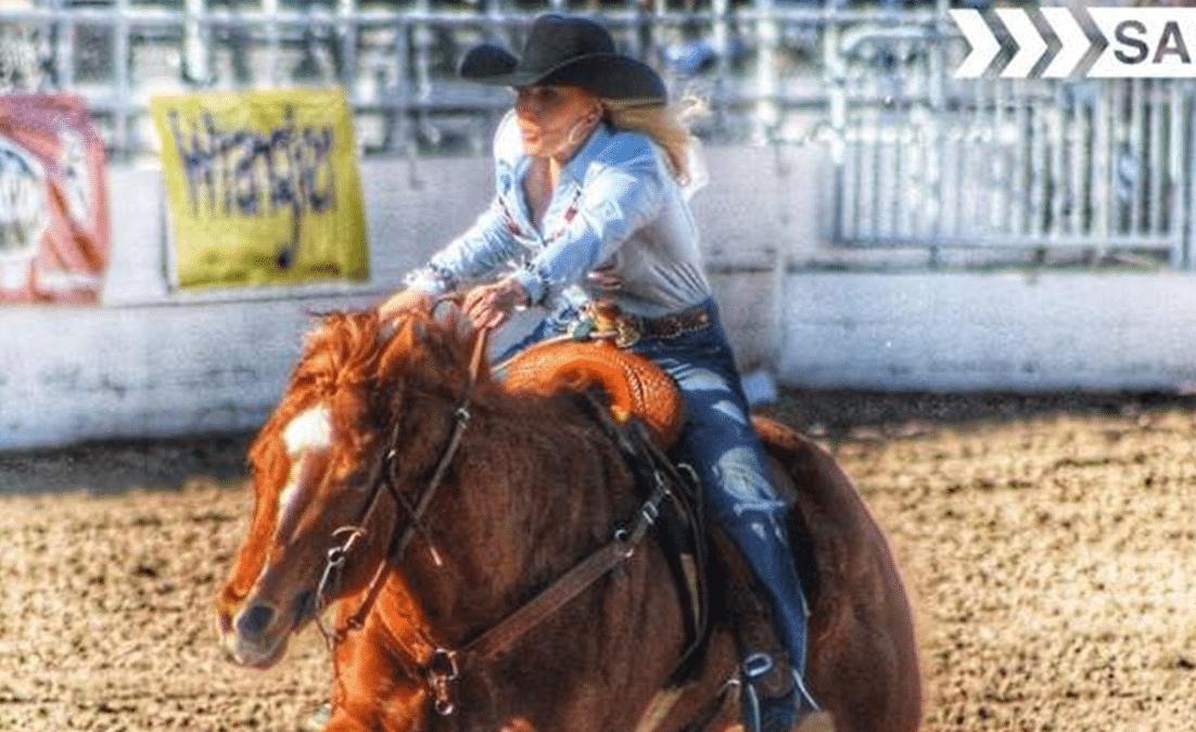 woman running barrels on sorrel horse