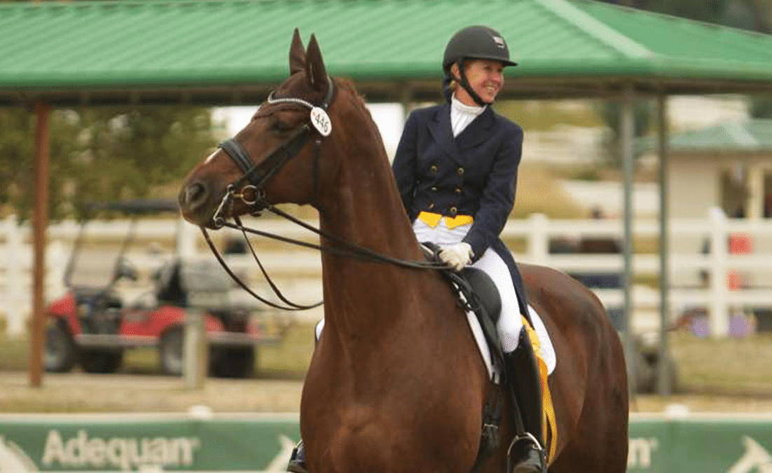 woman smiling on giant chestnut dressage horse