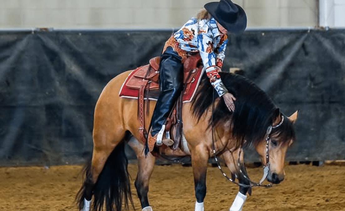 woman riding and patting dun ranch horse