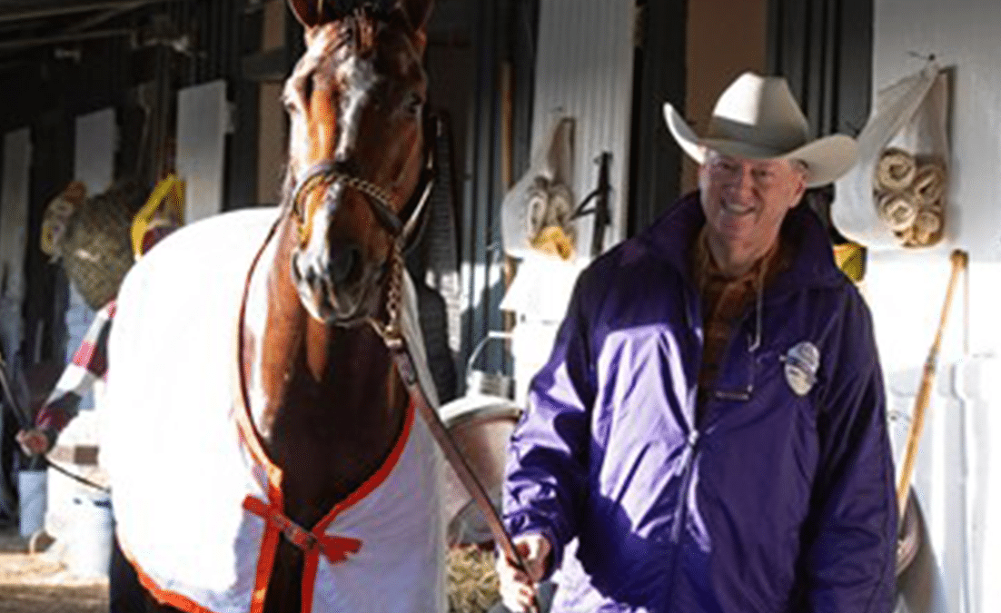 man in cowboy hat holding racehorse